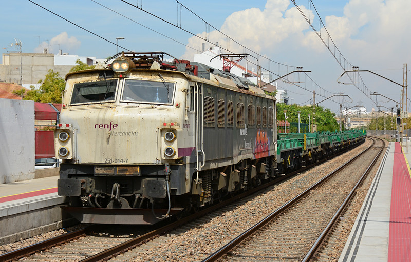 Renfe 251-014-7 is seen here in charge of an empty rake of steel coil wagons, passing through Massanassa having just worked up from the port of Valencia.
