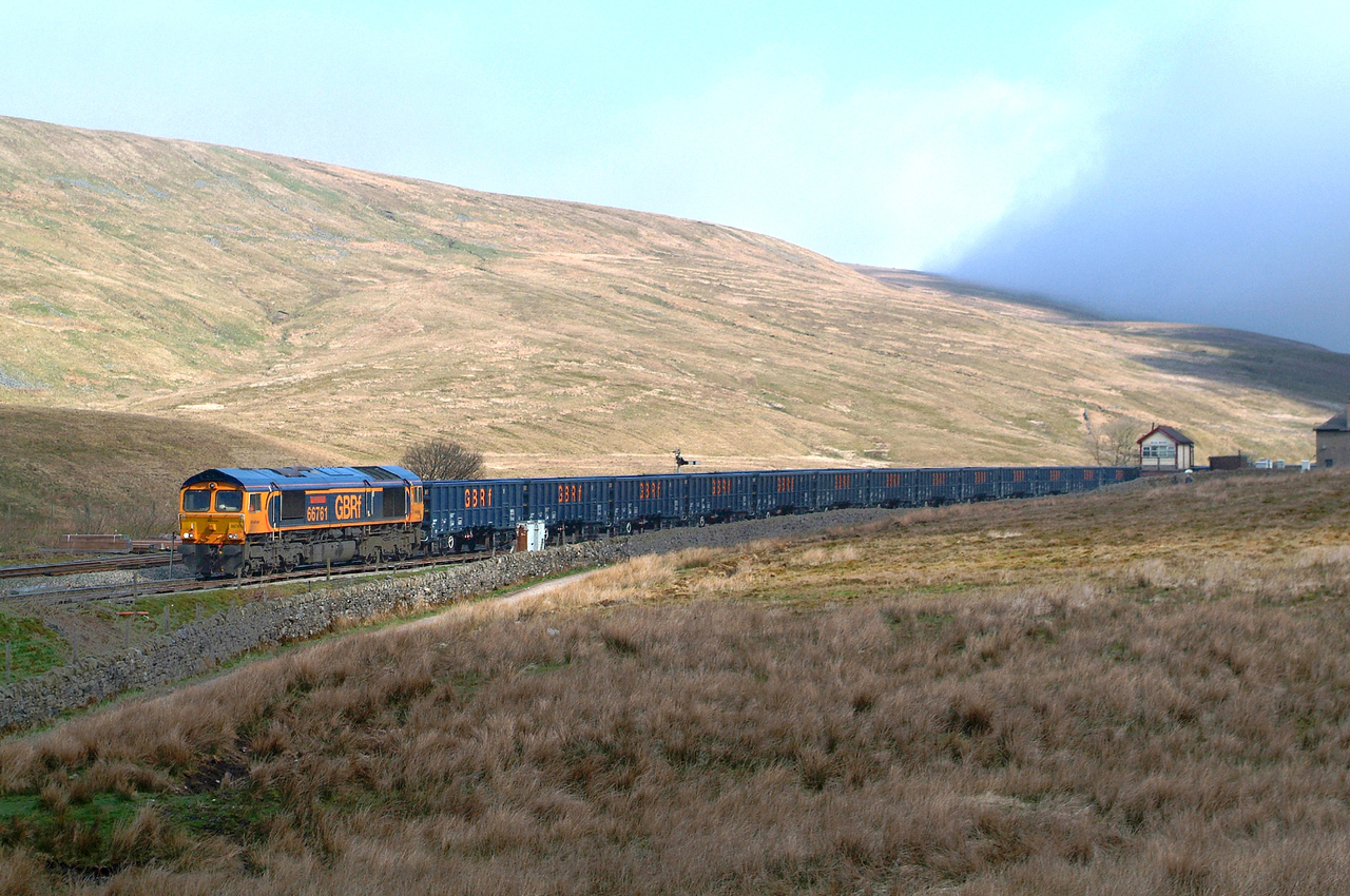"""Next and final morning. Friday. Clear blue at Garsdale but thick fog down below at Ribblehead Station and Viaduct. Sunny for most of the time on Whernside. It was """" sort  of """" sun for this shot..... just 3 SECONDS of it in the 50 minutes I stood there with the train in the loop before me. 66761 20th April with seconds ticking away before departure time.. At 10.18 it left ,and so did I , not waiting for the cement as the fog crept ever nearer.  I'm so pleased I made the effort to climb through it to capture this very unusual working .  6M99 09.53 Ribblehead VQ-Wellingborough Up TC."""