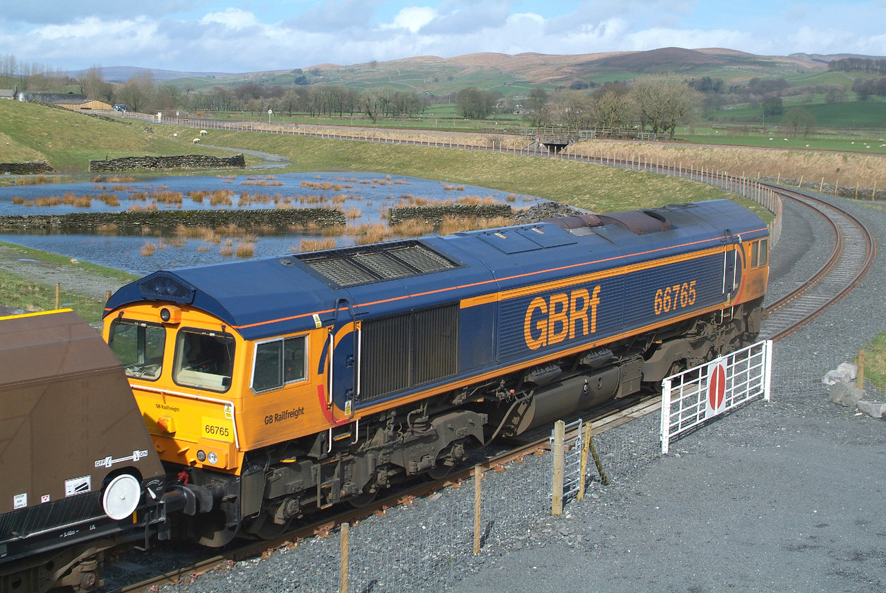 Having reversed its train back into the sidings , 66765 waits for the first wagons to start loading.
