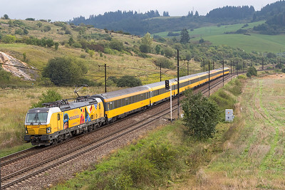 193 227 heads Regiojet service RJ 1012 08.00 Kosice to Praha approching Bešeňová. The locomotive carries adverts promoting the travel booking website of Regiojet owning company Student Agency. Wednesday 6th September 2017.