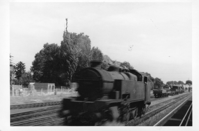 My only sighting of an ex SR W 2-6-4T class loco. Feltham's 31914, withdrawn later that month, was caught in camera from a passing train at Staines Central on 07/08/64.