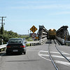 Back on the west coast of the South Island, the milk train is seen crossing one of two road/rail bridges north of Hokitika.