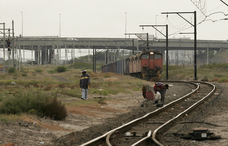 Pedestrians have taken to crossing the tracks as a shortcut. This guy is trying to lift a shopping cart with his belongings across the track as a tripleheaded set of electrics emerge from the freight underpass. The derail in the foreground is lined against the movement so the train will have to stop here.