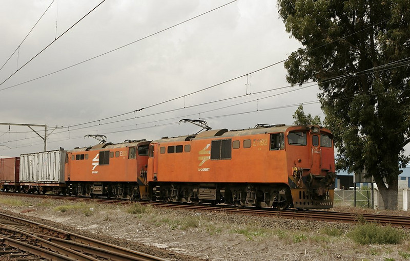 While the freight still threads onto the main, this pair of electrics speed past with a short container train.