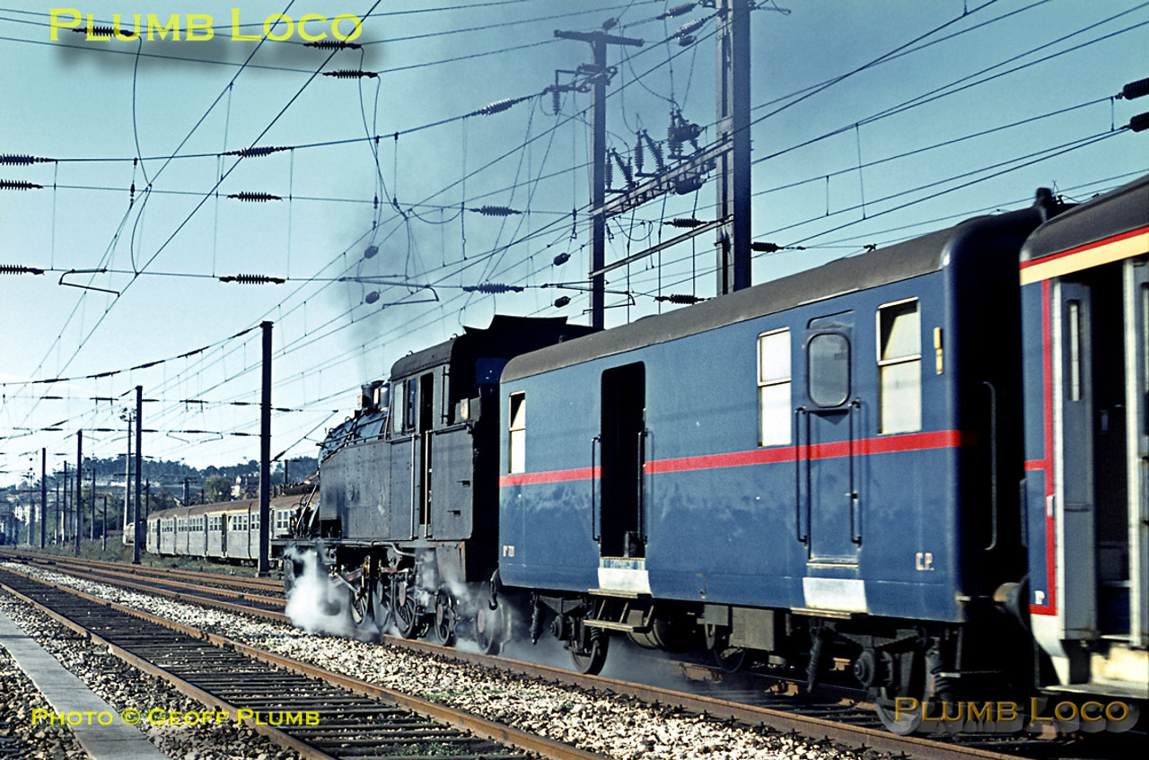 CP 2-8-4T No. 0184 (Henschel 1925) speeds past Contumil locomotive depot as it heads towards Porto Campanhã with the 08:55 train from Braga on Sunday 8th November 1970. An EMU of stainless steel stock can be seen in the sidings at the depot. Slide No. 5919.