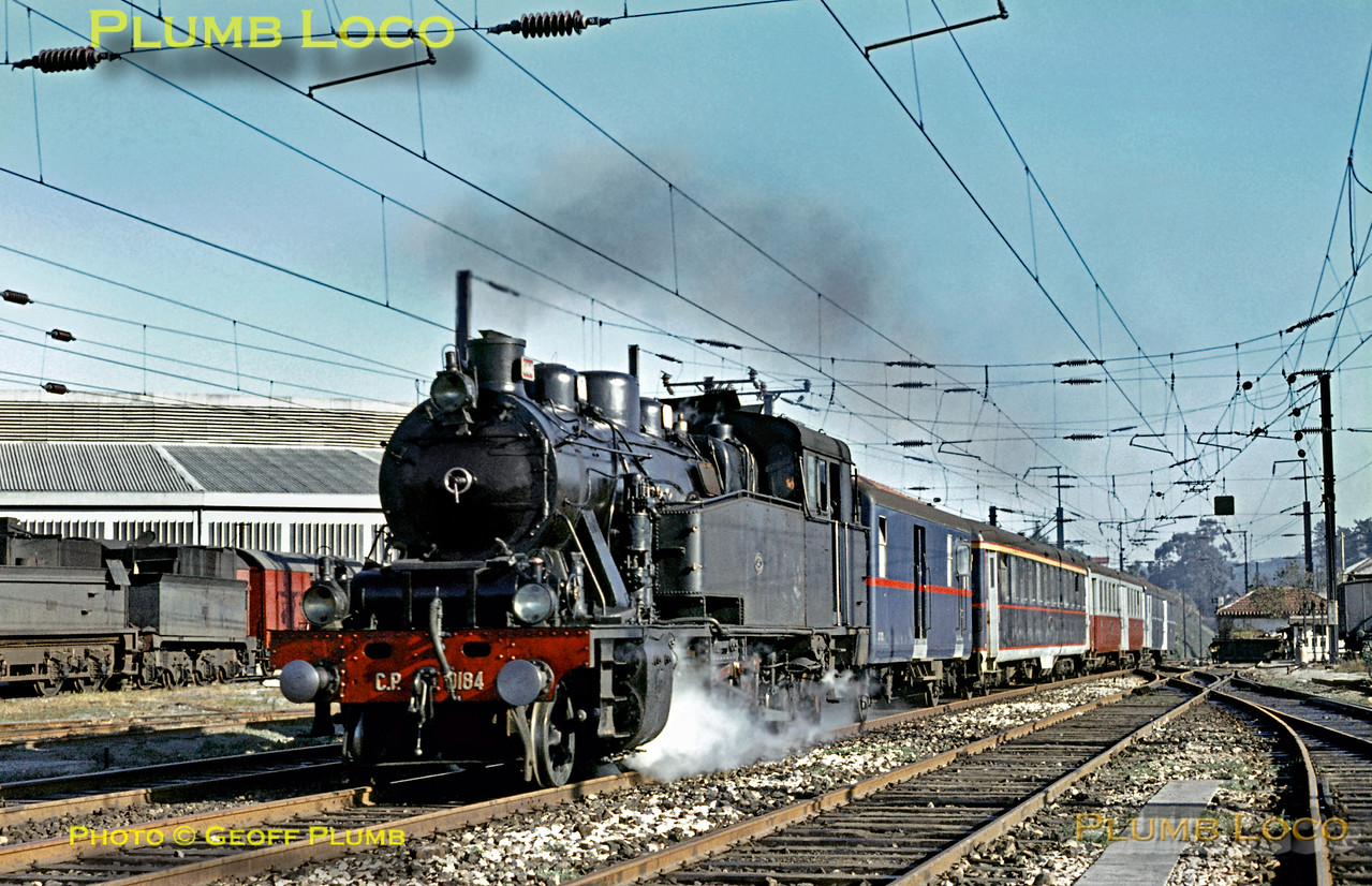 CP 2-8-4T No. 0184 (Henschel 1925) speeds past Contumil locomotive depot as it heads towards Porto Campanhã with the 08:55 train from Braga on Sunday 8th November 1970. Slide No. 5918.