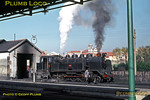 Seen from the platforms of the terminal part of the station at Povoa de Varzim, the small sub-shed plays host to Henschel 2-8-2T No. E142, while the crew prepare the engine for its next run back to Porto Trindade. Monday 3rd November 1969. Slide No. 4346.