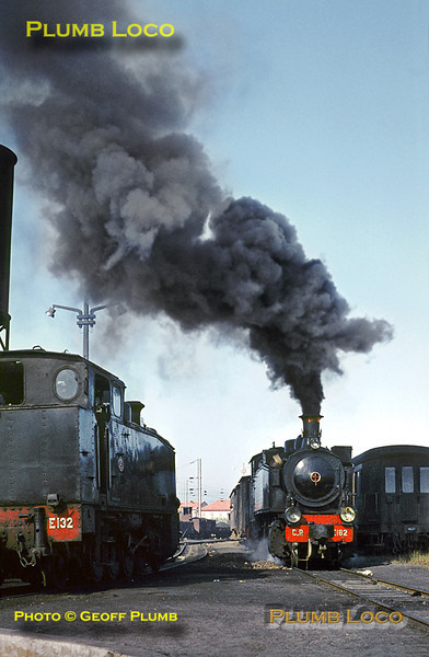 Mallet 2-4-6-0T No. E182 makes an incredibly smokey start away from Espinho station and is passing the depot where 2-8-2T No. E132 is about to go onto the turntable. E132's train is the 13:20 mixed train to Oliveira de Azemeis on Monday 9th November 1970. Slide No. 5982.