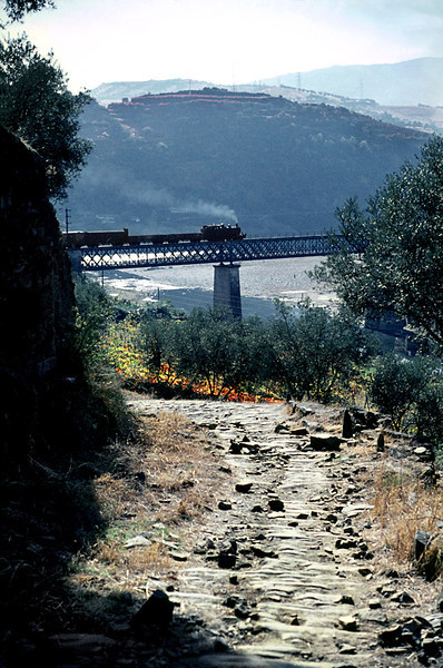An old stone roadway leads down from the hills through the vine terraces towards the Rio Corgo and Douro where CP Mallet 2-4-6-0T No. E206 is crossing the viaduct over the Rio Corgo. It is at the head of a mixed train from Chaves to Régua, due to arrive at 14:46 on Tuesday 3rd November 1970. Slide No. 5728.