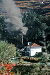 Mallet 2-4-6-0T No. E207 has stopped in the station at Carrazedo and the fireman is piling on coal for the climb ahead round the many curves to climb out of the valley and on to Vila Real, where this train was due to arrive at 13:15.  Thursday 5th November 1970. Slide No. 5812.