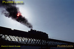 CP Henschel 1913 4-6-0 No. 292 attempts to blot out the sun with its oil-fired exhaust as it returns from the dam works at Bagausté with a works train to Régua, crossing the mixed-gauge viaduct over the Rio Corgo. Monday 2nd November 1970. Slide No. 5642.
