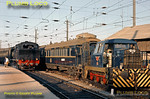 Steam and diesel under the wires at Porto Campanhã station on the evening of Sunday 8th November 1970. 2-6-4T No. 097 is the steam pilot doing some shunting on the left, while Sentinel 0-6-0 diesel hydraulic No. 1186 is on the right with a CIWL sleeping-car, making up an overnight train to Lisboa, perhaps? This engine was Class 1150, built in 1966. Slide No. 5956.