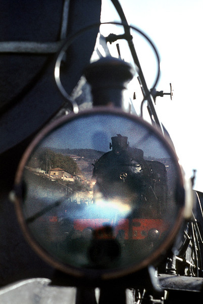 2-8-4T No. 0183 is seen reflected in the cracked glass of the oil headlamp on the bufferbeam of Borsig 4-6-0 No. 238, both sitting on shed at Régua on the morning of Tuesday 3rd November 1970. Slide No. 5707.