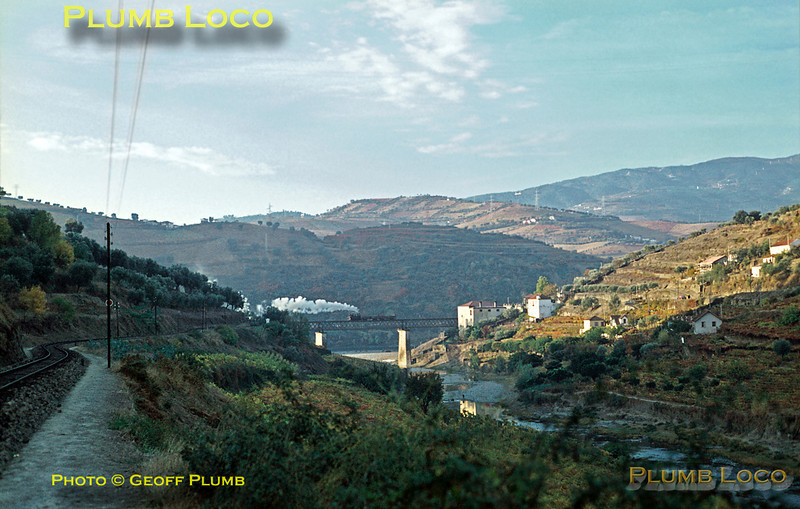 The sun is still low in the sky as 0-6-0T No. E54 crosses the viaduct over the Rio Corgo, just before it flows into the Douro. The loco is propelling a train from Corgo works to Régua and is seen from alongside the Corgo line from Régua to Chaves. Wednesday 4th November 1970. Slide No. 5745.