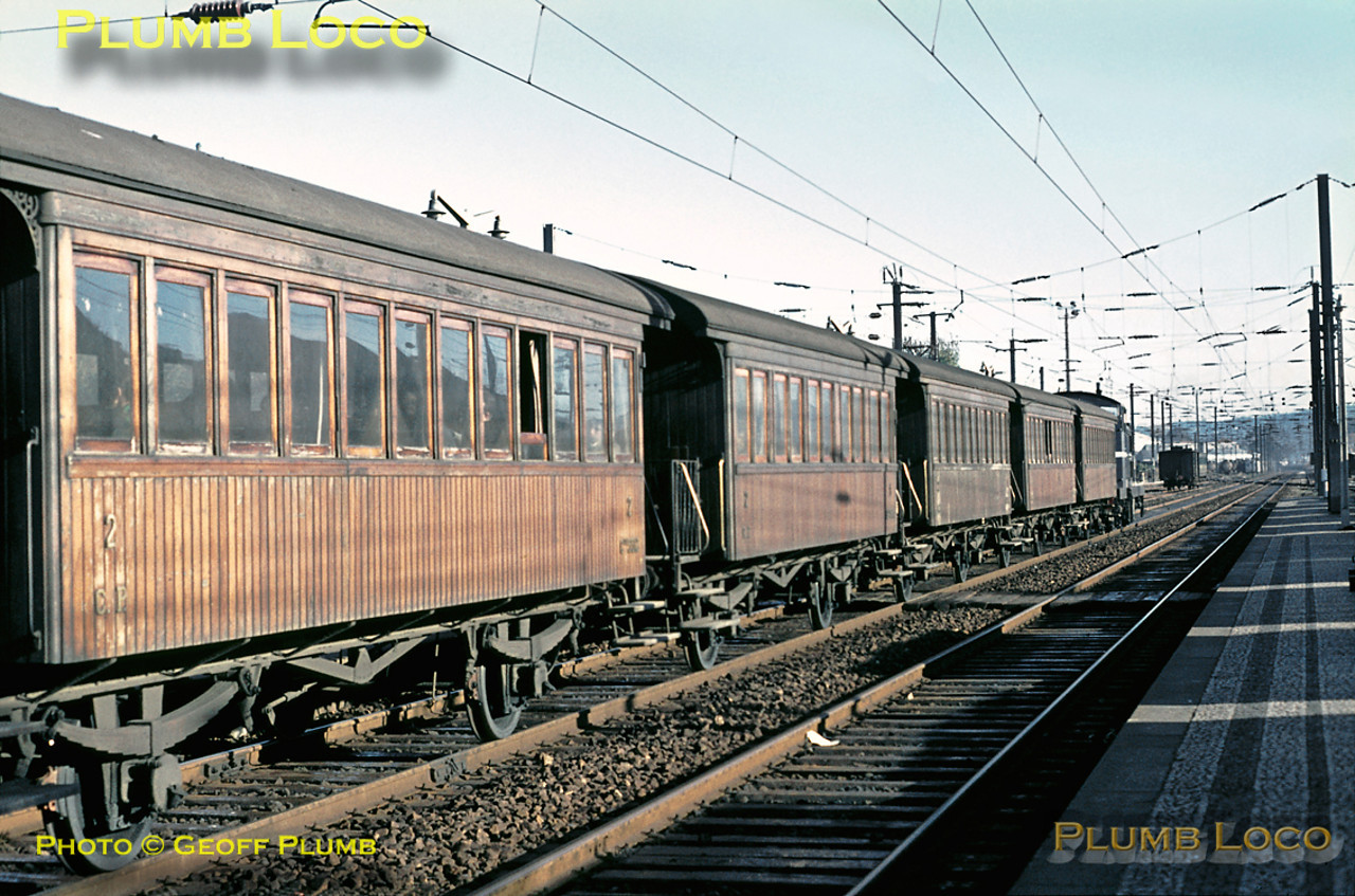 One of the 1400 series of English Electric Bo-Bo diesels is at the head of this wonderful train of antique matchboard wooden bodied four-wheel coaches with end balconies, about to depart northwards from Contumil station. Where it had come from and where it was going remain a mystery! The locomotive depot can be seen in the distance. Sunday 8th November 1970. Slide No. 5912.