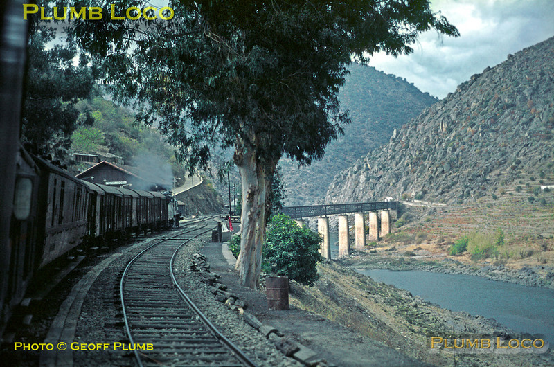 """Seen from the 12:32 mixed train from Pocinho to Porto, hauled by """"B12"""" No. 286, stopped in the station at Ferradosa. In the background is the viaduct over the Rio Douro, taking the railway onto the northern side. This viaduct has been demolished since the new dam was built further downstream, only the abutments still stand. The railway now continues for a little further on the north bank before crossing a new concrete viaduct, to a rebuilt Ferradosa Station. The old station still exists and the road in the background of this shot now uses the old trackbed to form a new access road to Taylor's Port Quinta at Vargelas (where the station is within the vineyard!). Saturday 7th November 1970. Note the very lightweight track - this was the reason for steam's survival in this area, the track being unable to take the axle-loading of the diesels until it was all relaid. Slide No. 5907."""
