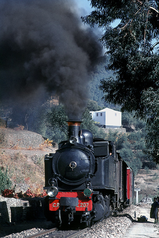 Mallet 2-4-6-0T No. E207 had stopped in the station at Carrazedo and is now well into the gradients round the many curves to climb out of the valley and on to Vila Real, where this train was due to arrive at 13:15.  Thursday 5th November 1970. A couple of the local population stand in the shade of a lineside tree to watch the train go by. Slide No. 5815.