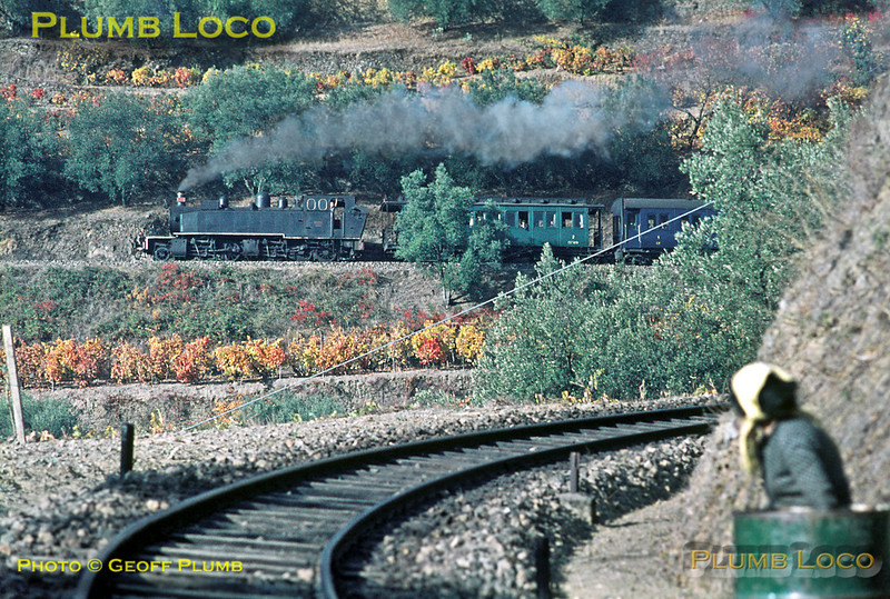 E205 has now climbed past the camera position alongside the track and has almost reached the top of the graded curves above Carrazedo, working the 10:21 train from Régua to Chaves. In the right foreground, a local resident is positioning a large water butt in readiness for the next move... Thursday 5th November 1970. Slide No. 5799.