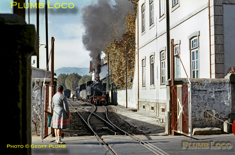 Having opened the level-crossing gates across the railway and put chains across the road, the lady crossing-keeper is now ready with her flags to see 2-4-6-0T Mallet No. E207 away from Vila Real station with the 10:21 train from Régua to Chaves on the metre gauge Corgo Line. Wednesday 4th November 1970. Slide No. 5769.