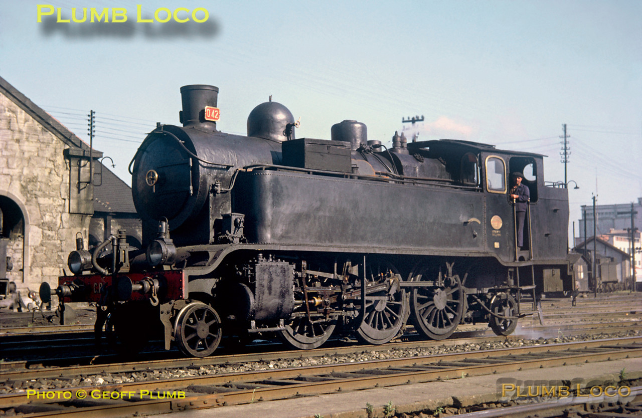 From the Geoff Plumb Collection of original slides. CP 2-6-2T No. 042 is seen outside the depot alongside Porto Campanha station and is in steam. This loco was built by Cockerill in 1907. Saturday 9th May 1964. The engine was reported as being at Vila Nova de Gaia in 1969, set aside for preservation, but whether this happened or not, I do not know. Photo by John F. Robinson. Collect Slide No. JFR32.