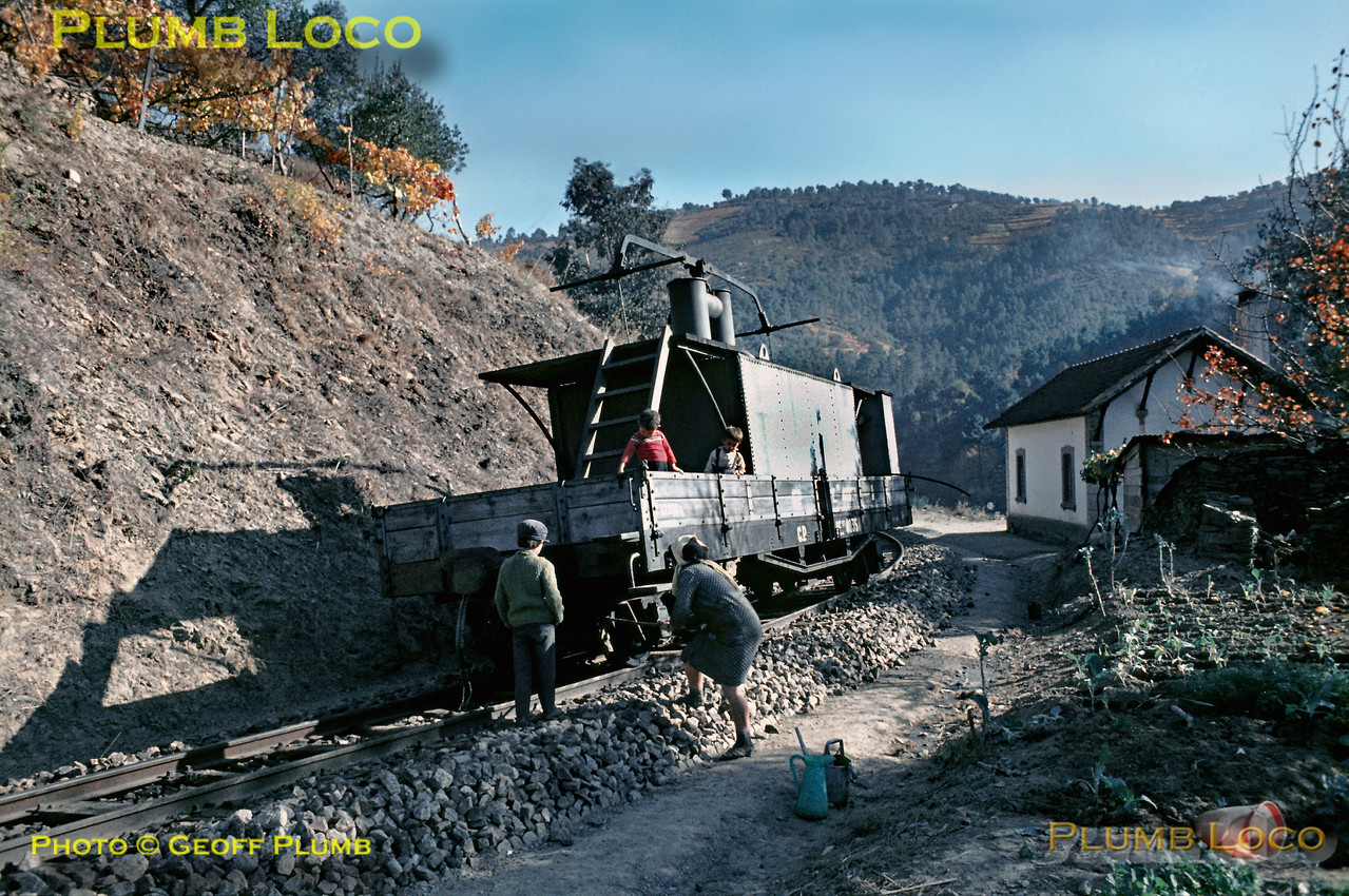 The water carrier has run down by gravity under the control of the brakesman and stopped at rail-side houses as it made its way back to Carrazedo. Here, the family has filled all sorts of containers, including a large water butt no longer in the picture, and they are helping to get the wagon rolling again with the aid of crowbars! Note there is no fencing or means of isolating the house and its vegetable plot from the railway. Whether this practice still continues to this day I do not know! Thursday 5th November 1970. Slide No. 5810.