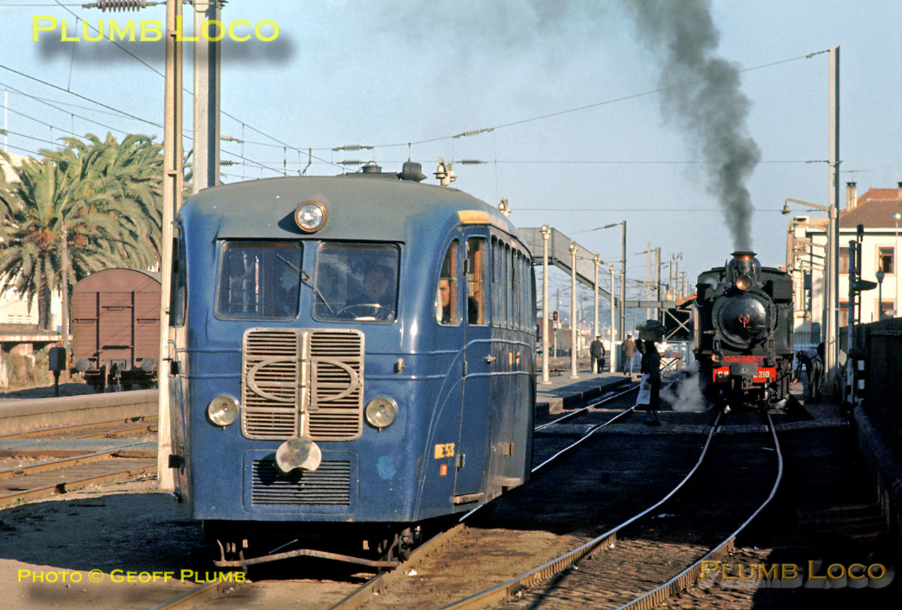 """2-4-6-0T Mallet E210 sits in the joint narrow gauge and broad gauge station at Espinho with the 11:00 train for Oliviera de Azemeis. Alongside is literally a """"Railbus"""", ME 53, complete with what appears to be a steering wheel (!), departing for Sernada do Vouga. Monday 9th November 1970. Slide No. 5967."""