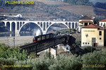 """CP metre gauge Henschel 2-4-6-0T Mallet No. E208 crossing the mixed-gauge viaduct over the Rio Corgo with a Corgo line passenger train, the 10:21 from Régua to Chaves. It has the branch signal at the end of the viaduct in the """"off"""" position and will turn  north as soon as it has left the bridge. In the background is the roadbridge over the Rio Douro and beyond that an abandoned lattice girder bridge. Tuesday 3rd November 1970. Slide No. 5676."""