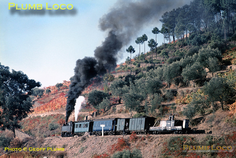 Mallet No. E205 has climbed round the loops and curves above Carrazedo on its way to Vila Real with the 10:21 train from Régua. It had collected a water-carrier wagon at Carrazedo and has now stopped to uncouple this wagon, the brakesman just climbing down from the Baggage Van. Once uncoupled, the train carried on its way, while the water wagon rolled by gravity back to Carrazedo, stopping at rail-side houses to fill up their water supplies as it did so! Thursday 5th November 1970. Slide No. 5802.