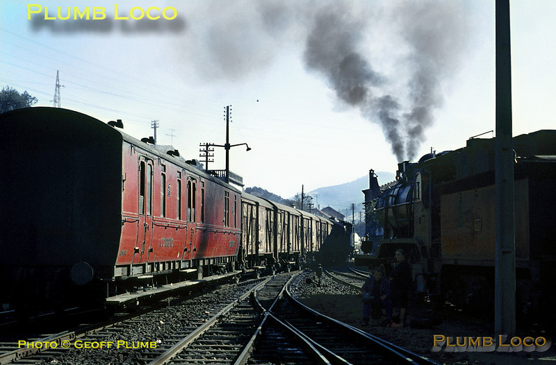 Whilst 4-6-0 CP No. 286 brews up on the right of the picture, 2-6-4T No. 076 shunts some wagons and a Postal Coach to add to the 09:37 train from Porto, which was diesel hauled to Régua. Once the diesel has come off the train and the additions made, No. 286 will take the train forward to Barca d'Alva at 12:35. Note one of the engine crew having a picnic lunch while seated on a point lever in the shade of the engine! Tuesday 3rd November 1970. Slide No. 5712.