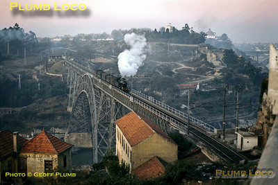 CP Henschel 2-6-4T No. 095 crosses the Rio Douro from Vila Nova de Gaia to Porto on the Ponte Dona Maria Pia, designed by Eiffel and built in 1876/77. It is working the 07:30 stopping passenger train from Espinho to Porto Campanhã, 9th November 1970. The bridge was closed and replaced by a modern concrete structure, the Ponte São João in 1991, though it is still in situ. The matching road bridge can just be seen in the right background. Slide No. 5962.