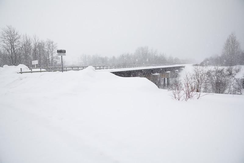 Railway bridge across Store Creek in Moosonee during heavy snowfall.