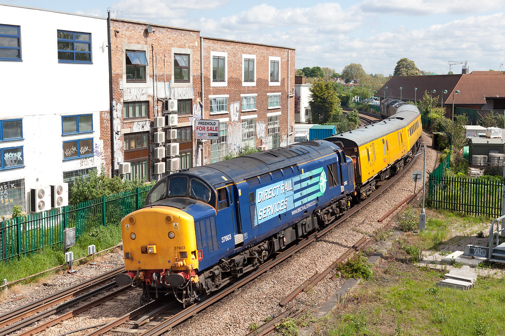A photograph that probably reflects the modern railway scene, palisade fencing, buddleia, mobile phone masts and graffiti. 37603 approaches Richmond with the  1Q18 So 07.57 Old Oak Common-Derby RTC via the north London line Network Rial measurement train. Included in the consist is 'mentor' coach 975091
