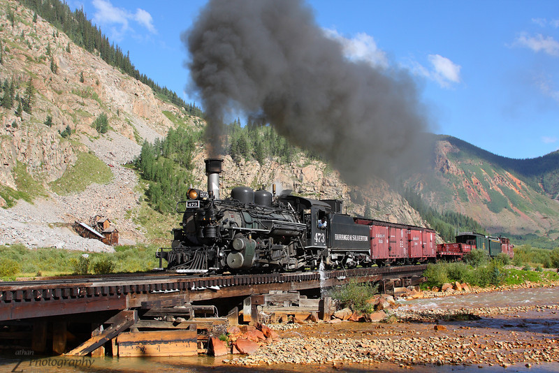 Durango and Silverton 473 with a mixed extra crossing the Animas River south of Silverton, Colorado.