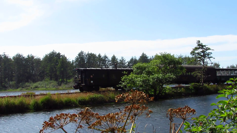 It's a rare sunny, warm day on the Oregon Coast. Running northbound alongside highway 101 is an Oregon Coast Scenic Railway train, heading for Rockaway Beach and led by 1925 Alco 2-6-2 No. 25, formerly of the McCloud River Railroad in northern California. The train ambles over a causeway across a lagoon, interrupting some folks fishing on the embankment.