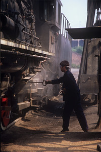 Worker cleans the ash pan of an SY engine, his shoes are basically slippers.