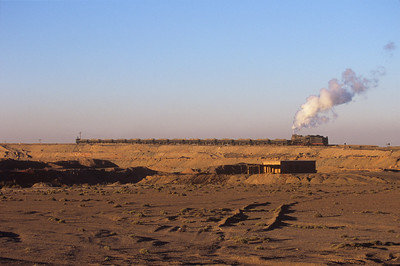 A JS heads to dump a load of overburden in the morning light, its last run before the crew change.