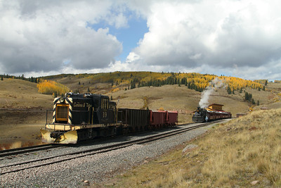 Ex-US Navy GE diesel-electric switch engine #19 sits at Osier with 3 car loads of ballast with the west bound passenger train and fall colours in the background.