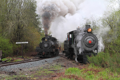 Polson Logging engine #70 sits on the siding as Willamette #2 passes with a log train.