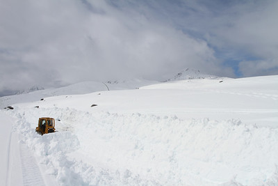 A bulldozer tries to make life easier for the rotary plow in a deep rock cut at Canadian Shed. At this point the snow is about 20 feet deep and heavily packed.