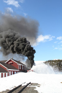Trying to pound through the last mound of snow at Bennett, BC, the rotary stalls with a jet black plume of smoke.
