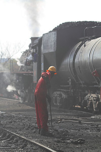 A breeze kicks up the smoke and dust as a worker rakes up the coal chunks line-side.