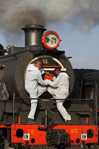 Looking like doctors going to the E.R, two workers try to open the door for the smoke box on engine 12.
