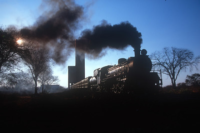 Selebi Phikwe: Botswana - Class 19D 4-8-2 starts to pull out with a full load just before dusk.