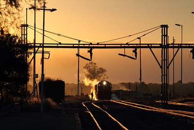 Morning glint in Plumtree.  A diesel engine pulls the Garratt steam locomotive and consist into the depot at Plumtree.