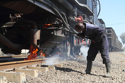 "A crew member works to clear a clinker on #519, a class 14a Garratt, while stopped at a location known as ""Cement"" in Zimbabwe."