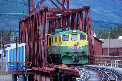 "Loaded with railfans on their way to Skagway, AK, WP&Y diesel locomotive #100 crosses the bridge at Carcross, With upgrades/refurbishing taking place, this engine will soon have a ""facelift"" like some of its brethren."