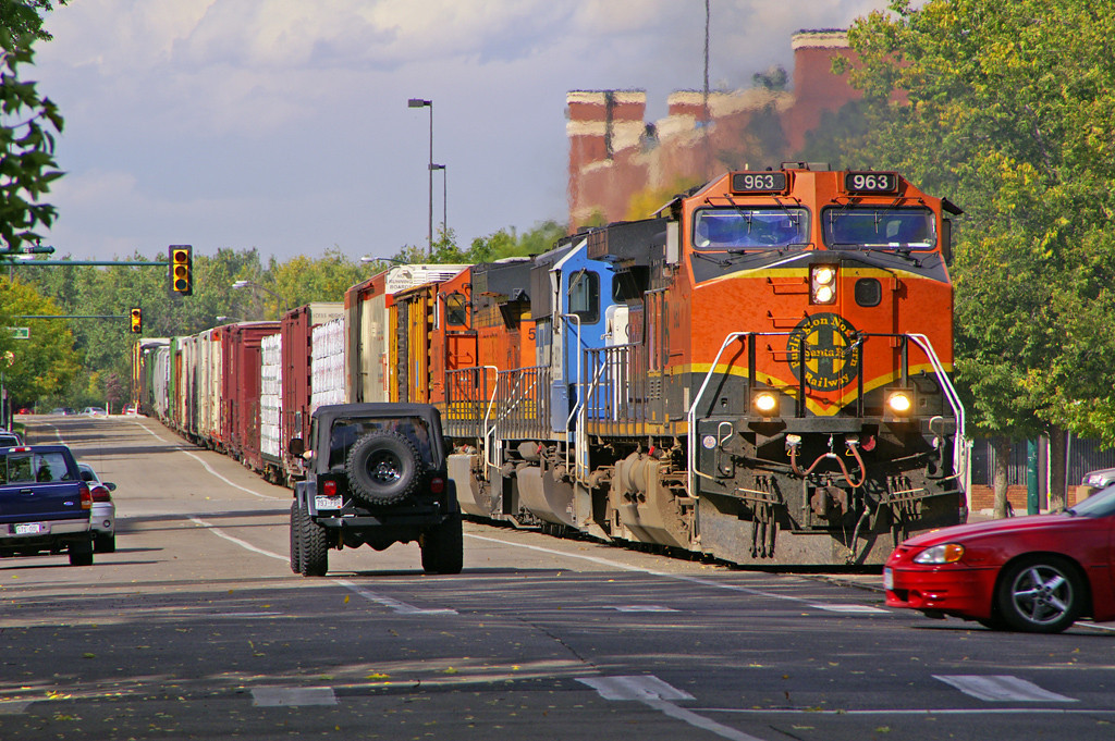 Freight trains run down the middle of the street in Fort Collins, CO fortunately the driver of the red car moved.