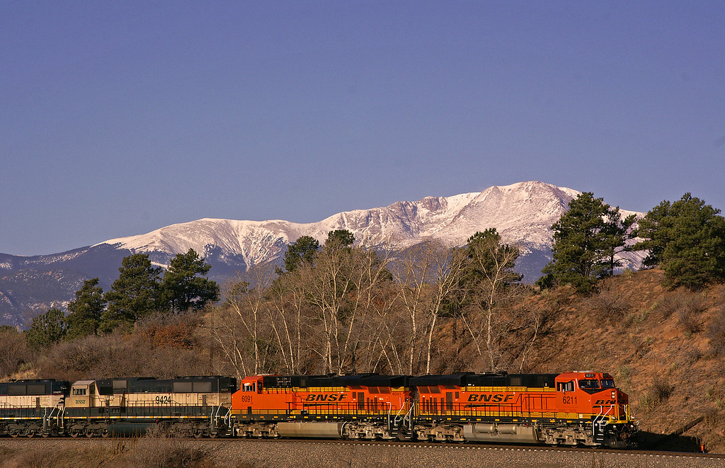 A BNSF freight train cruises north towards Denver under the ever watchful eye of Pikes Peak.