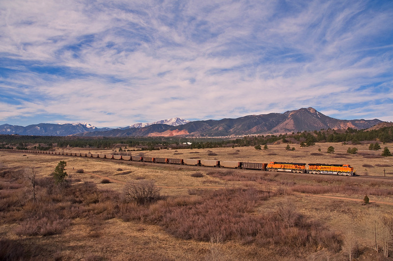 A BNSF coal empty passes through the United States Air Force Academy along the Front Range of the Colorado Rockies. The snow covered peak is Pikes Peak.