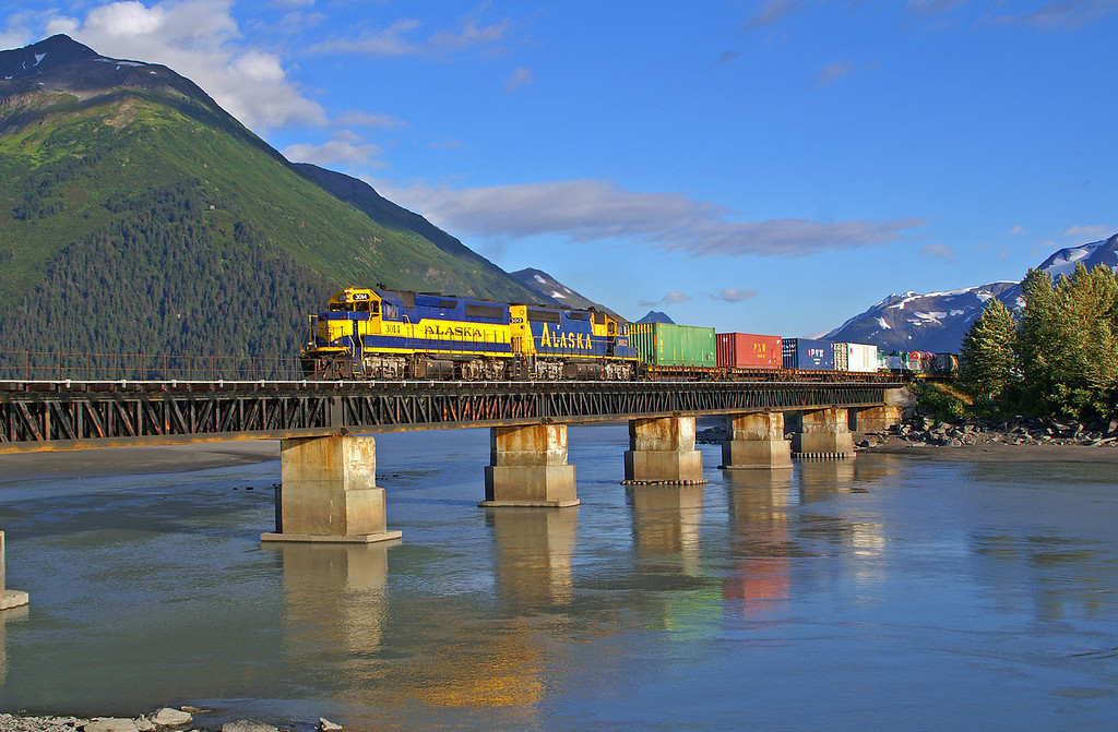 On a beautiful day in Alaska an Alaskan barge train destined for Anchorage crosses the 20 Mile River.